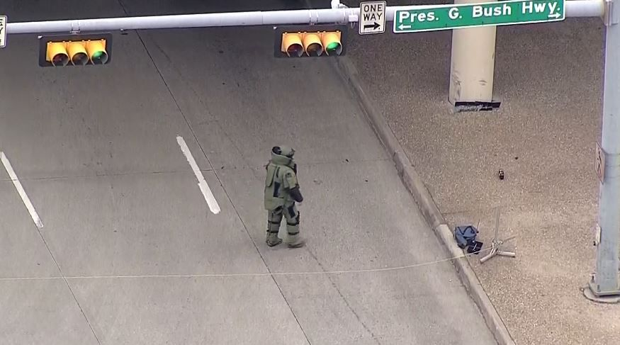 A Plano bomb squad officer moves in on a suspicious package found under the President George Bush Turnpike.