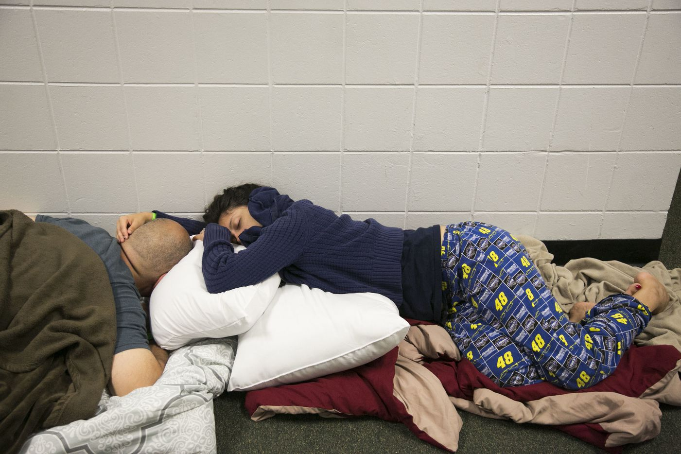 Yaya Lopez holds her fiance, Howard Lopez, while they sleep in a hallway at John Hopkins Middle School on Sunday, Sept. 10, 2017, in St. Petersburg, Fla. The school filled classrooms and hallways with people evacuating before Hurricane Irma makes landfall.