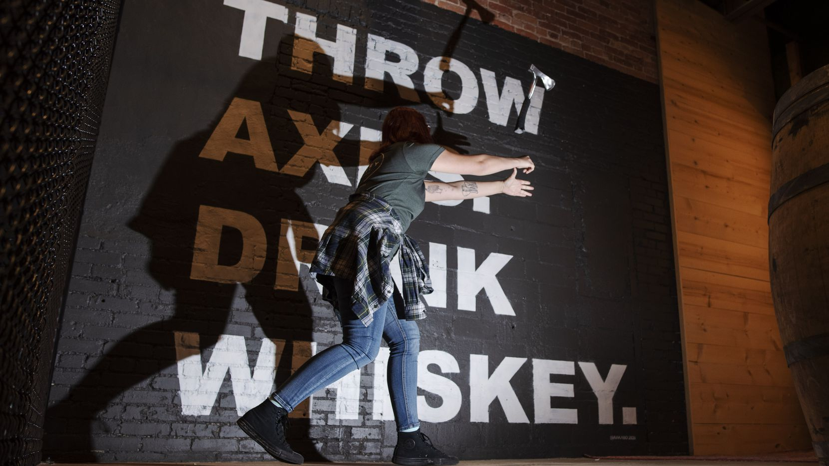 Elisa Grace, a staffer at Whiskey Hatchet, demonstrates her two-handed throwing technique at the new bar in Deep Ellum.