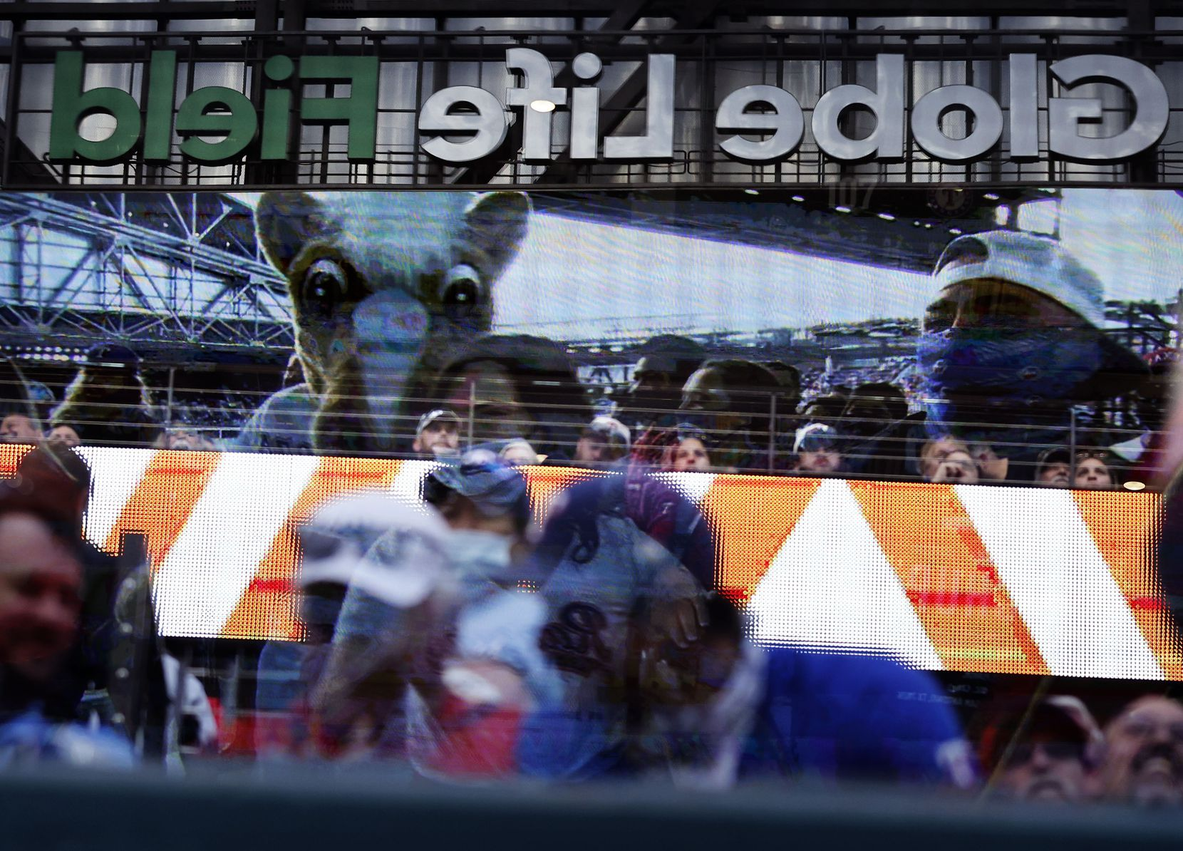 A reflection of the video board and stadium are seen in the plexiglass above the Toronto Blue Jays dugout at Globe Life Field in Arlington, Monday, April 5, 2021. The Texas Rangers were facing the Toronto Blue Jays in their home opener. The Rangers lost, 6-4. (Tom Fox/The Dallas Morning News)