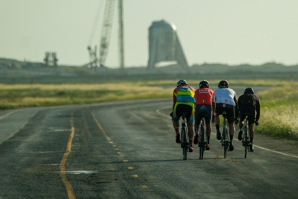 A group of cyclist ride on Boca Chica Boulevard toward the Starhopper spaceraft at the SpaceX Space Launch Facility in Boca Chica, Texas, on Saturday, Sept. 28, 2019.