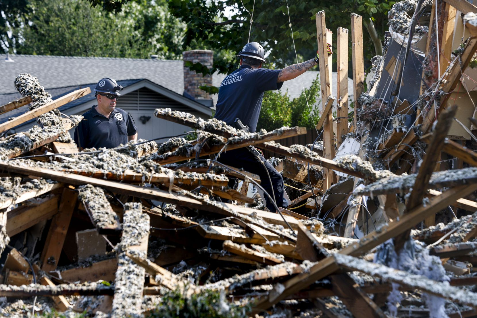 Inspectors from the Plano Fire Marshall office examine the site of a house explosion on the 4400 block of Cleveland Drive in Plano, Texas, on Tuesday, July 20, 2021. The explosion, which happened Monday, left six people hospitalized and was likely due to an isolated gas leak, fire investigators said.