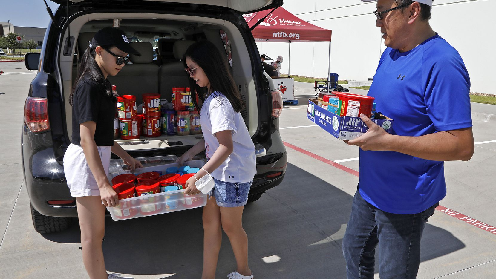 McKinney resident James Huang (right) unloads peanut butter with help from 12-year-olds Betty Lou (left) and Vivian Zhou, both of Allen, during a collection drive to battle hunger. Huang launched a community service effort called the Nihao Movement that organized Saturday's event in Plano in partnership with the North Texas Food Bank. Such charity is viewed by some Asian American leaders as a pillar of efforts to combat hate toward Asian Americans and Pacific Islanders.