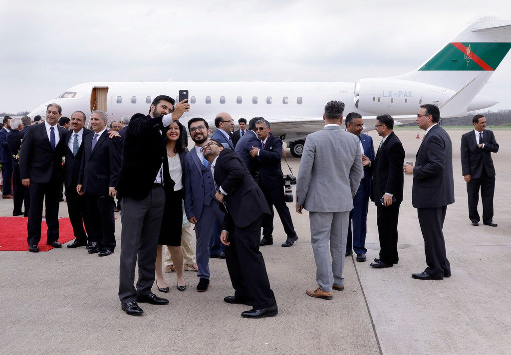 Attendants crowd around the plane of the Aga Khan and take selfies after his departure from the Sugar Land Regional Airport Sunday.