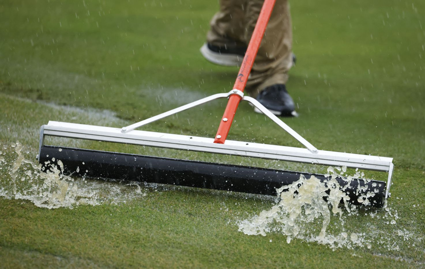 Rainwater is pushed off the green on the 17th hole during round 4 of the AT&T Byron Nelson  at TPC Craig Ranch on Saturday, May 16, 2021 in McKinney, Texas. (Vernon Bryant/The Dallas Morning News)