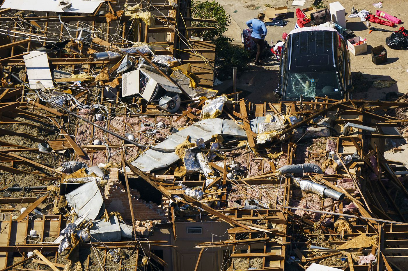 A woman stands in amidst the rubble of a damaged home near Royal Lane and North Central Expressway in an aerial view of tornado damage on Monday, Oct. 21, 2019, in Dallas.