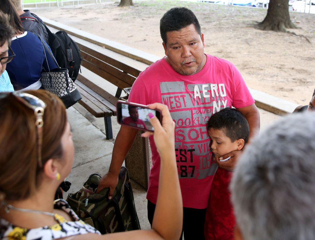 Jose Banda, an evacuee from Dickinson, Texas, speaks to the media with his son Justin Banda, 7, after arriving at the mega-shelter outside the Kay Bailey Hutchison Convention Center in Dallas on Tuesday, Aug. 29, 2017.
