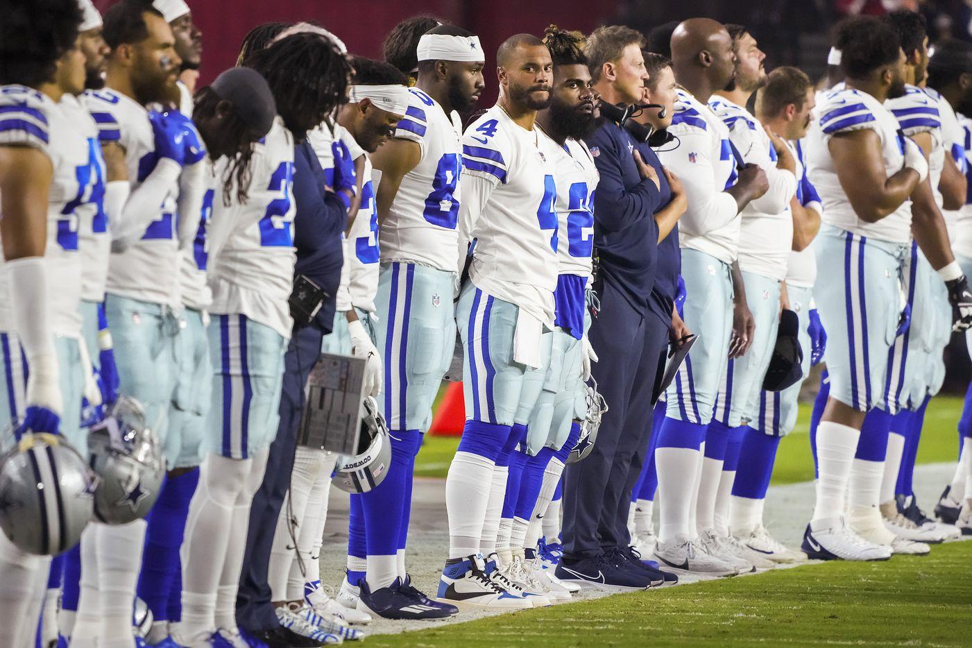 Dallas Cowboys quarterback Dak Prescott (4) and running back Ezekiel Elliott (21) stand for the national anthem with teammates before a preseason NFL football game at State Farm Stadium on Friday, Aug. 13, 2021, in Glendale, Ariz.