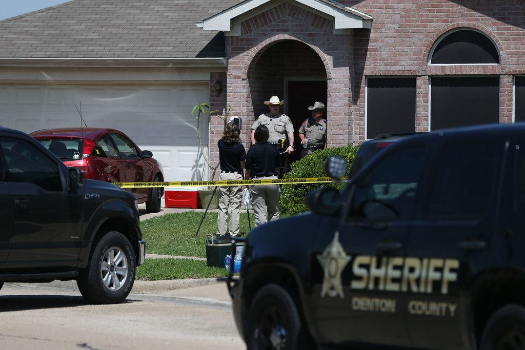Denton County Sheriff's officers investigate a crime scene at a home where five people were killed.