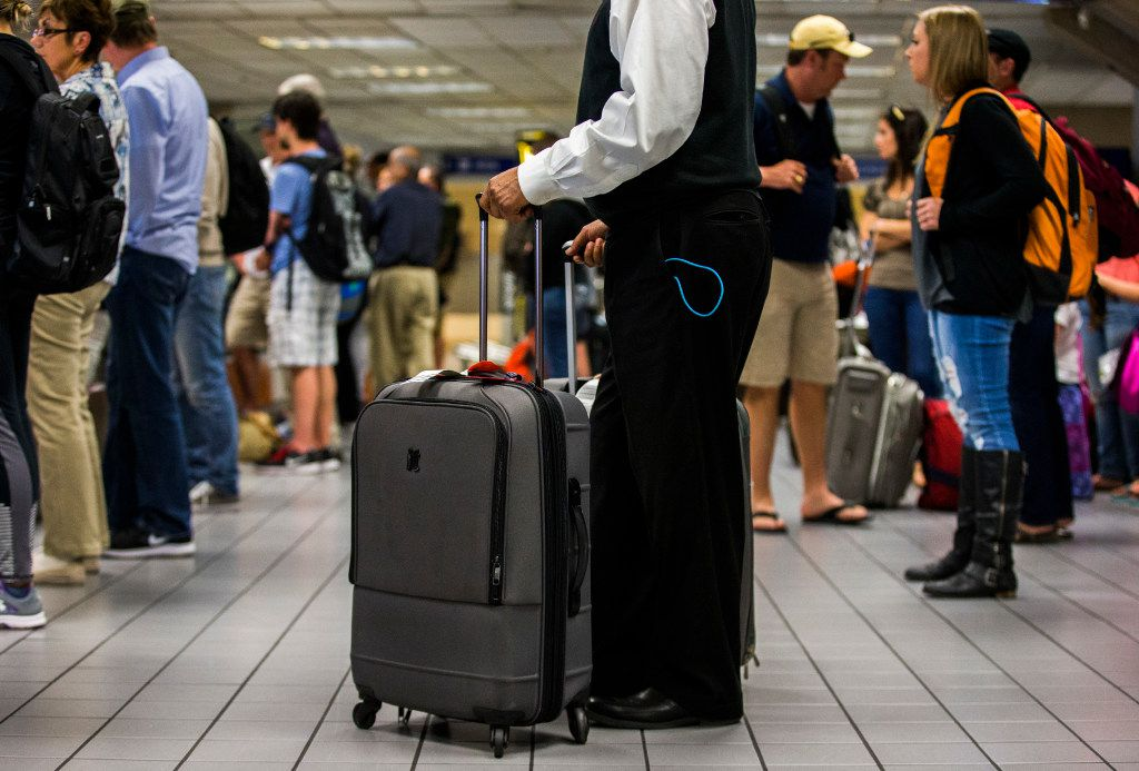A traveler stands with his bags as luggage moves around a baggage claim at Gate C on Friday, March 10, 2017 at DFW international Airport in Dallas. (Ashley Landis/The Dallas Morning News)
