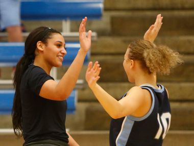 Hurst L.D. Bell guards Myra Gordon (15), left, shares a high five with Jaidyn Carter (10) following their 82-53 victory over Arlington Bowie to advance. The two teams played their Class 6A bi-district girls basketball game at Grand Prairie High in Grand Prairie on February 17, 2020.