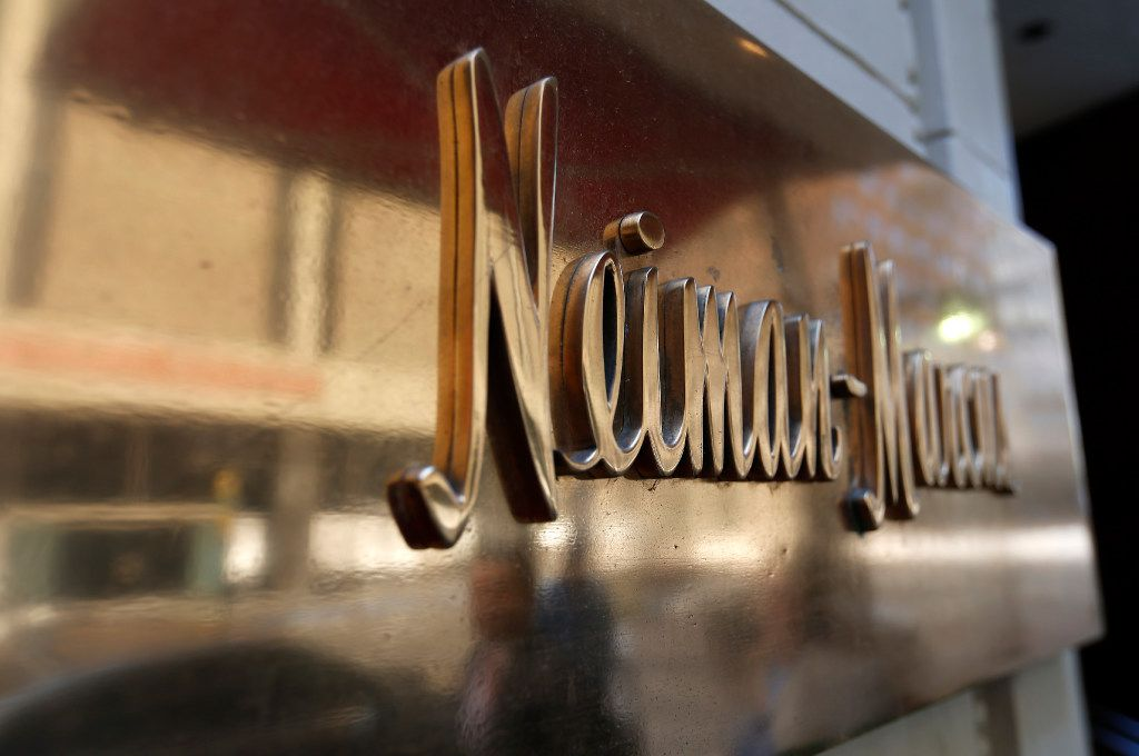 Pedestrians are reflected in a sign of Neiman Marcus on Commerce Street in downtown Dallas.