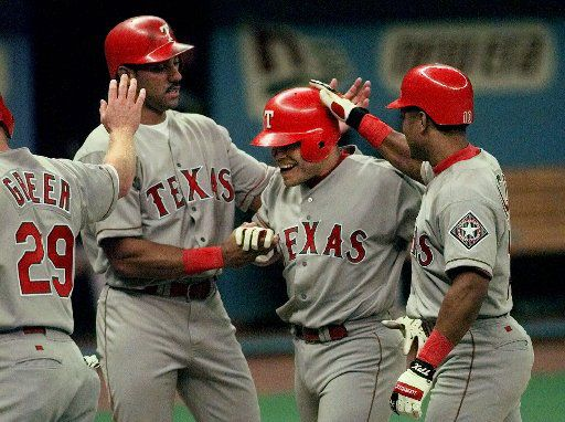 ORG XMIT: S116513B3_WIRE Texas Rangers' Ivan Rodriguez, second right, is greeted at the plate by the teammates who scored on his third-inning grand slam against the Seattle Mariners Tuesday, April 13, 1999 in Seattle. Rodriguez' homer, his second of the game, scored teammates Rusty Greer (29), Juan Gonzalez, second left, and Luis Alicea.