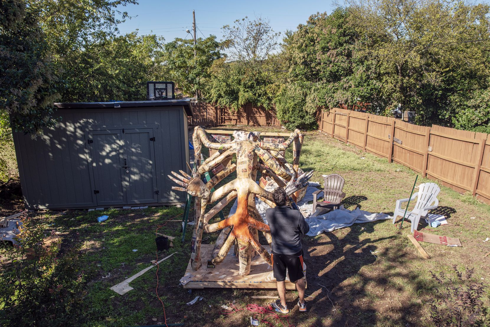 Artist Giovanni Valderas adds glue to a giant skeleton sculpture in his back yard in Dallas on Friday.