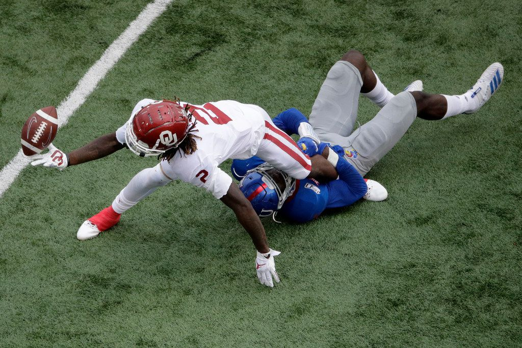 Kansas linebacker Azur Kamara (5) tackles Oklahoma wide receiver CeeDee Lamb (2) as he passes off the ball during the first half of an NCAA college football game Saturday, Oct. 5, 2019, in Lawrence, Kan. (AP Photo/Charlie Riedel)