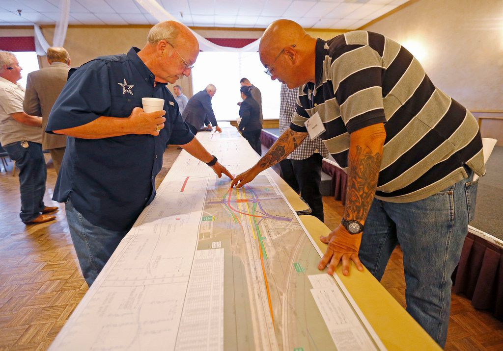 Rowlett resident Jim McKissick (left) asks questions of Mark Hull, an environmental specialist with the Texas Department of Transportation during a public hearing about planned Interstate Highway 30 frontage roads held Thursday at Rowlett's Hella Shrine. (Jae S. Lee/The Dallas Morning News)