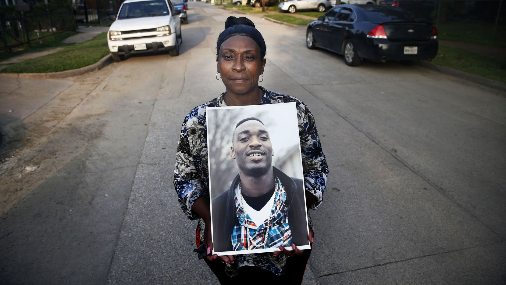 Rena Hightower poses with a portrait of her nephew Michael Tilley in front of her house in West Dallas. Tilley was killed in March.
