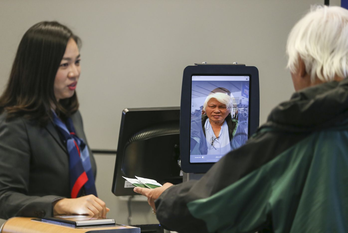 Gate agent Erica Shin assists as passengers board an American Airlines flight to Tokyo Narita International Airport using facial biometric scanning Tuesday, Aug. 27, 2019 in Terminal D of DFW Airport. The iPad device, which is currently only in use for international travelers, matches faces with the U.S. Customs and Border Protection (CBP) database, which includes passport photos. The information collected is transmitted only to CBP and not to independent airlines.