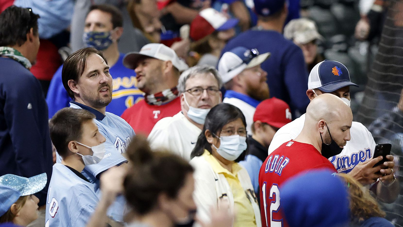 Texas Rangers fans, some with and without masks watch an exhibition game in the seventh inning at Globe Life Field in Arlington, Texas. The Rangers were facing the Brewers, Monday, March 29, 2021.
