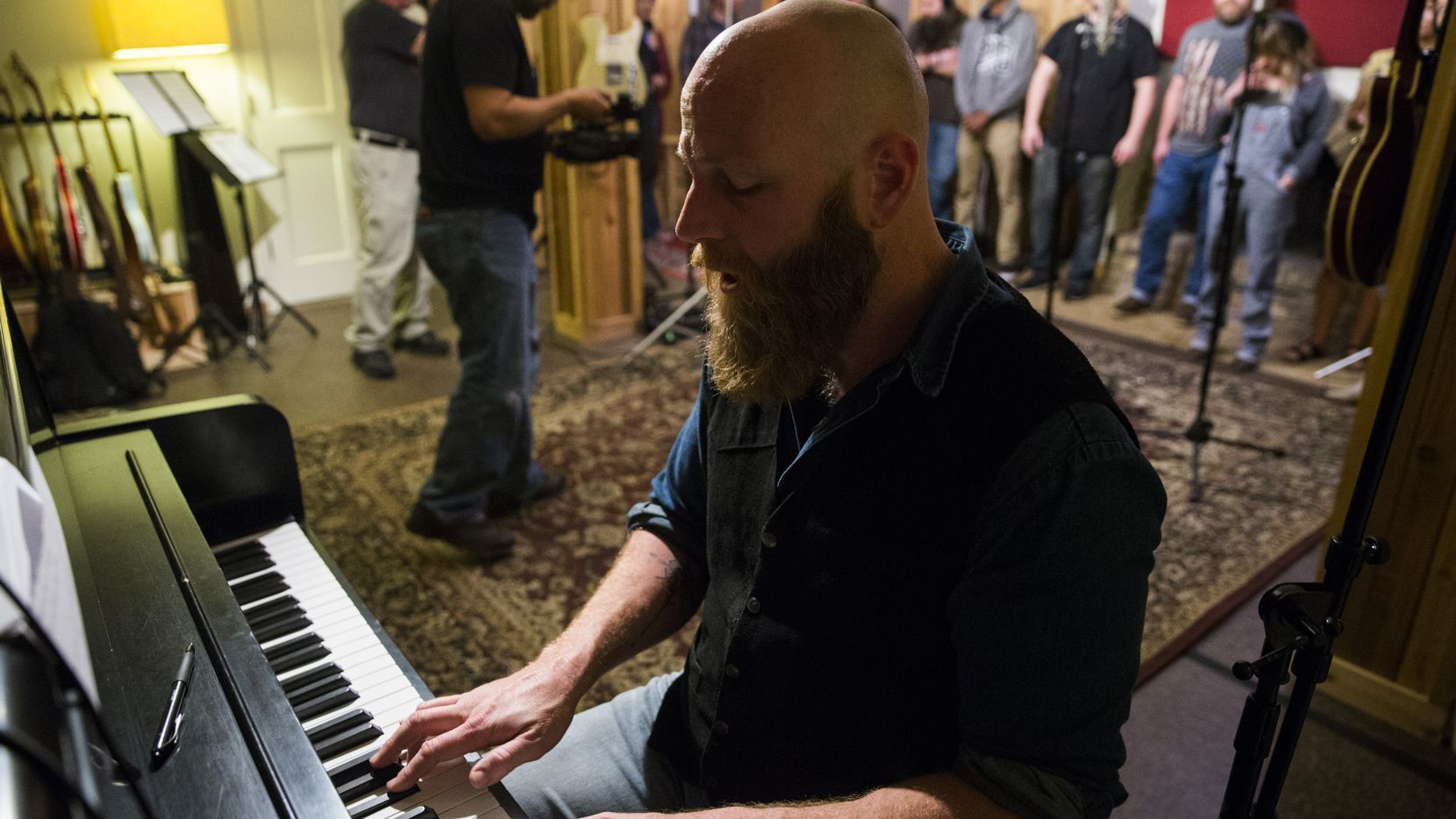 "Dan Johnson plays piano as local musicians record background vocals for their version of Willie Nelson's ""Living in the Promiseland"" in Fort Worth, before social distancing rules went into effect. The recording will be released as a fundraiser to help refugees."