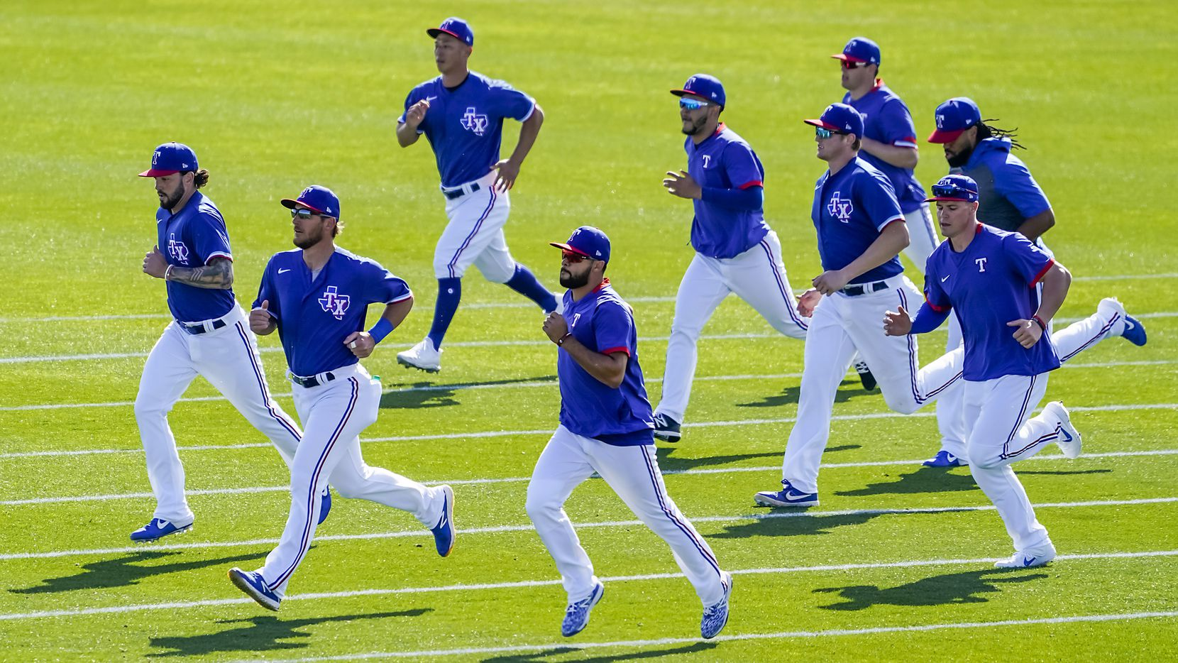 Texas Rangers position players run on a practice field during a spring training workout at the team's training facility on Wednesday, Feb. 19, 2020, in Surprise, Ariz. Pictured (from left to right) are catcher Blake Swihart, catcher Jeff Mathis, outfielder Rob Refsnyder (top), infielder Isiah Kiner-Falefa (bottom), infielder Anderson Tejeda, catcher Sam Huff, infielder Nick Solak (top), outfielder Scott Heineman (bottom) and outfielder Henry Ramos.