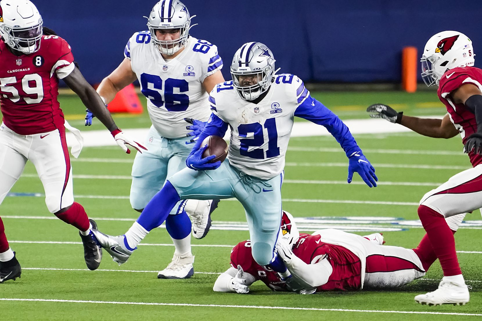 Dallas Cowboys running back Ezekiel Elliott (21) breaks through the Arizona Cardinals defense during the first quarter of an NFL football game at AT&T Stadium on Monday, Oct. 19, 2020, in Arlington. (Smiley N. Pool/The Dallas Morning News)