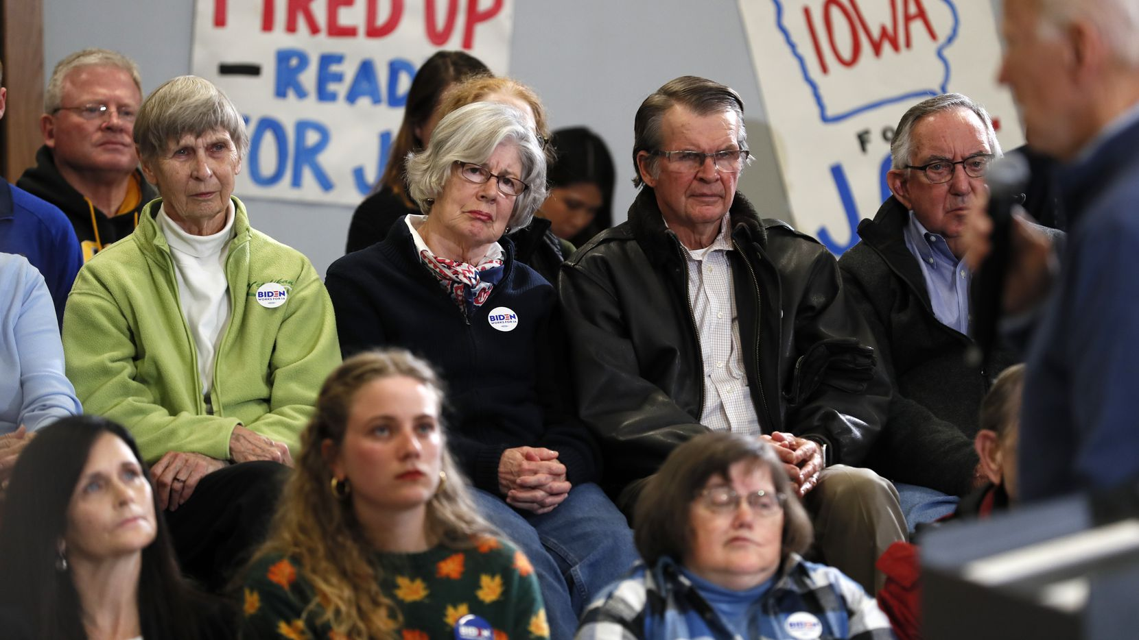 Audience members listen to Democratic presidential candidate and former Vice President Joe Biden, right, speak during a town hall meeting Friday, Nov. 22, 2019, in Winterset, Iowa. (AP Photo/Charlie Neibergall)