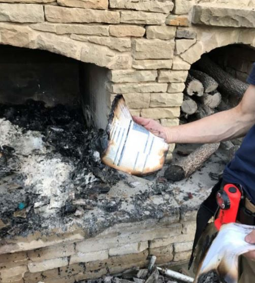 A firefighter displayed a partially burned medical record found in an outdoor fireplace at the home of Mark and Melissa Kuper in October 2017. The fire spread to their $1.6 million home, destroying it.