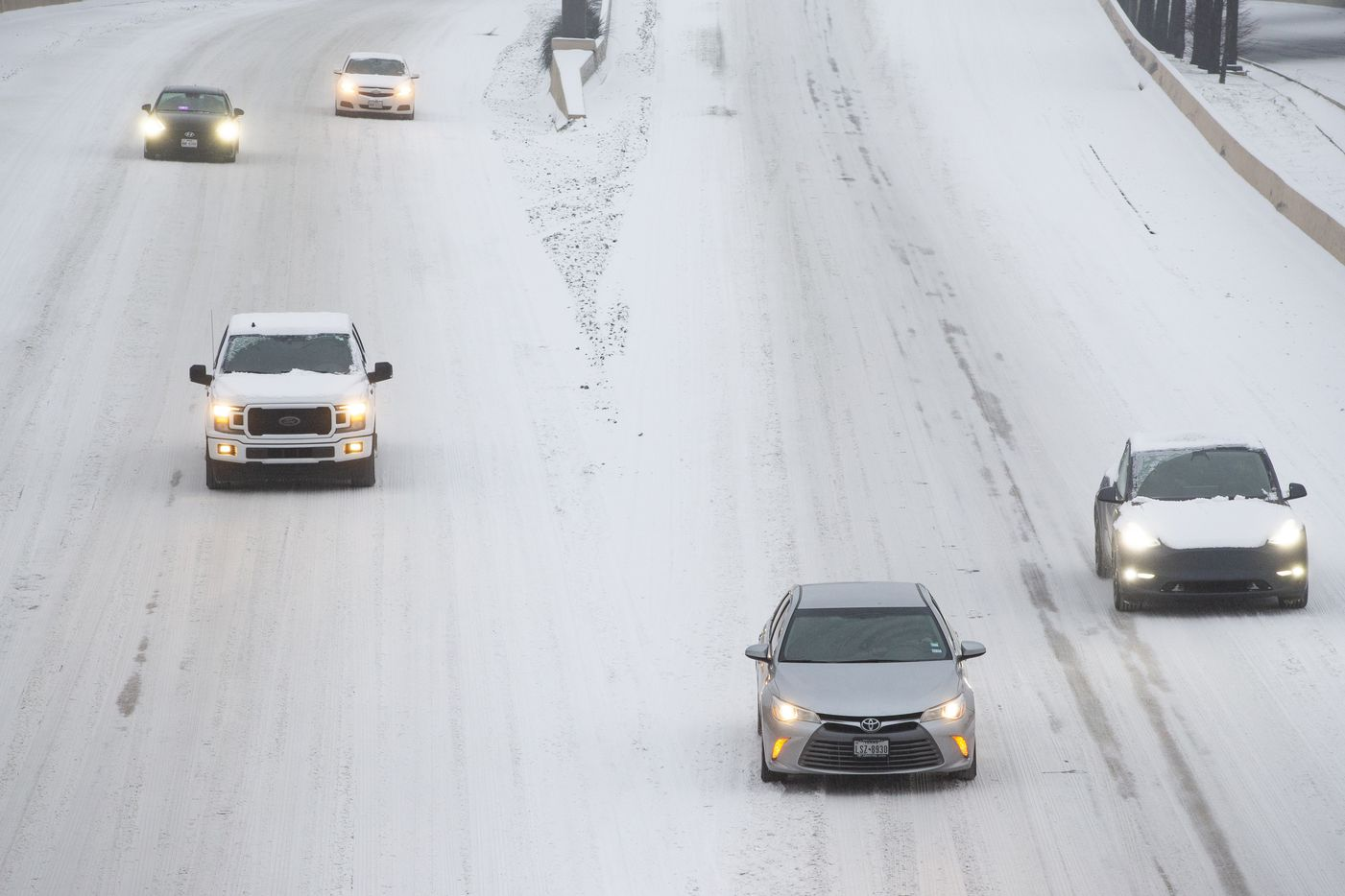 Traffic seen on a snowy and icy North Central Expressway in Dallas on Wednesday, Feb. 17, 2021. Millions of Texans have lost power amid this record-breaking winter storm.