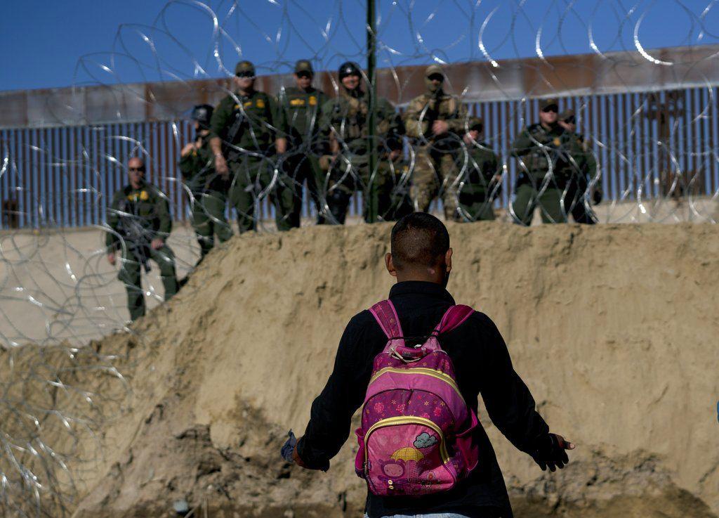 Un migrante hondureño conversa con agentes fronterizos de Estados Unidos del otro lado de un alambre de cuchillas despúes de que rociaran gas lacrimógeno a los migrantes que intentaron cruzar a Estados Unidos desde Tijuana, México, el domingo 25 de noviembre de 2018. (AP Foto/Ramon Espinosa)