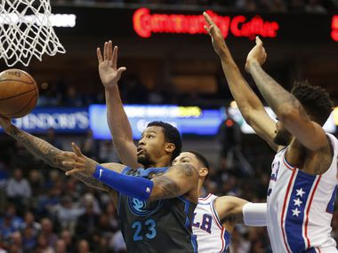Dallas Mavericks guard Trey Burke (23) attempts a layup in front of Philadelphia 76ers guard Ben Simmons (25) and Philadelphia 76ers forward Jonah Bolden (43) during the first half of play at the American Airlines Center in Dallas on Monday, April 1, 2019.