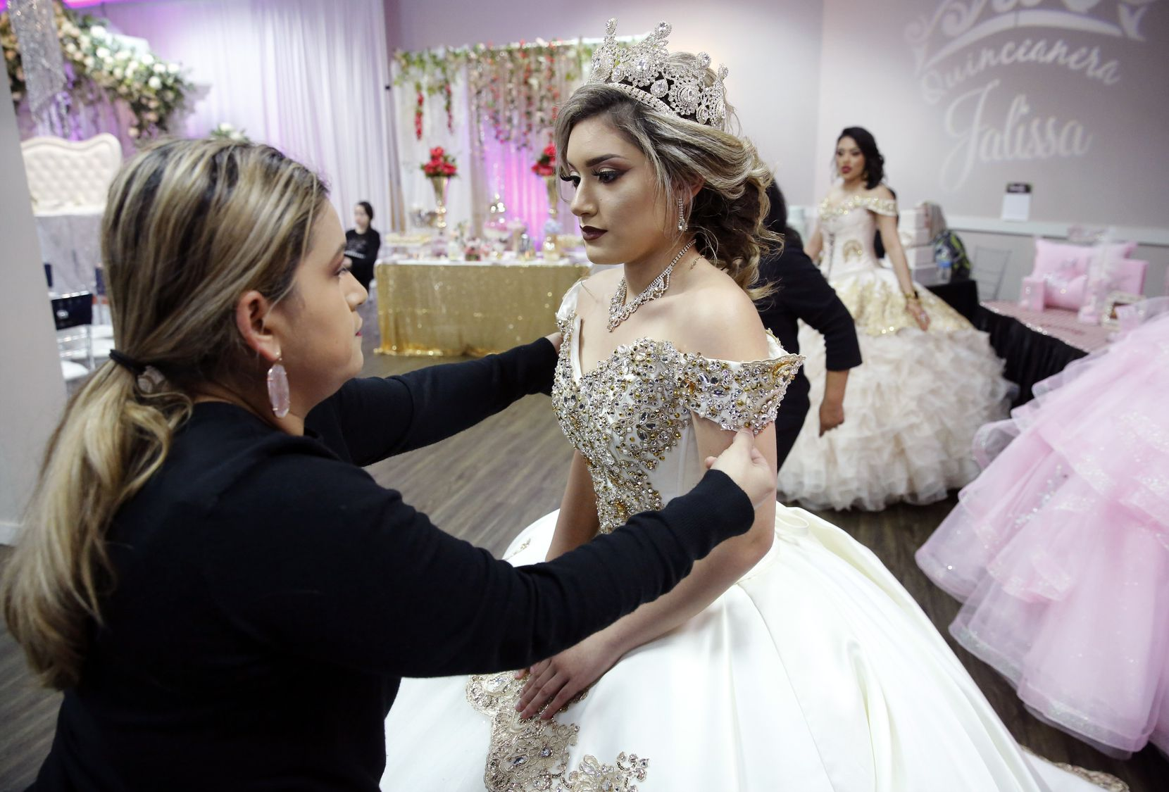Ana Garcia fixes a quinceañera dress modeled by daughter Jessica Monge during the Las Lomas Quinceañera & Wedding Expo held at the Irving Banquet Halls in Irving, Texas, Sunday March 15, 2020. Attendance was low.