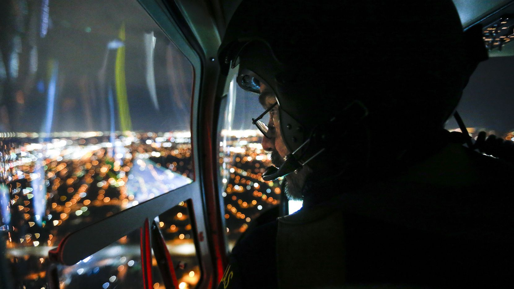 Assisting ground units in hunting a stolen vehicle, Dallas police Senior Cpl. Mark Colborn looks out the window or Air One.