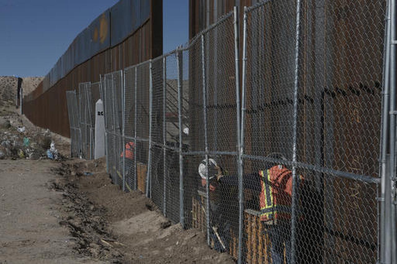 Unos trabajadores continúan laborando para eregir una barda más alta en la frontera entre México y Estados Unidos, la cual separa los pueblos de Anapra, México y Sunland Park, Nuevo México, el miércoles, 25 de enero del 2017. (AP/CHRISTIAN TORRES)