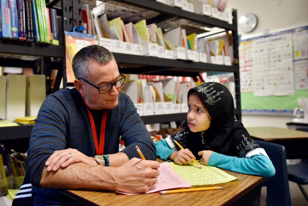 Second grader Bibi Rabialam practices her reading skills with volunteer Douglas Dyment during a program for refugee students at Lee A. McShan Jr., elementary school in Dallas, on Dec. 15, 2016. Ben Torres/Special Contributor
