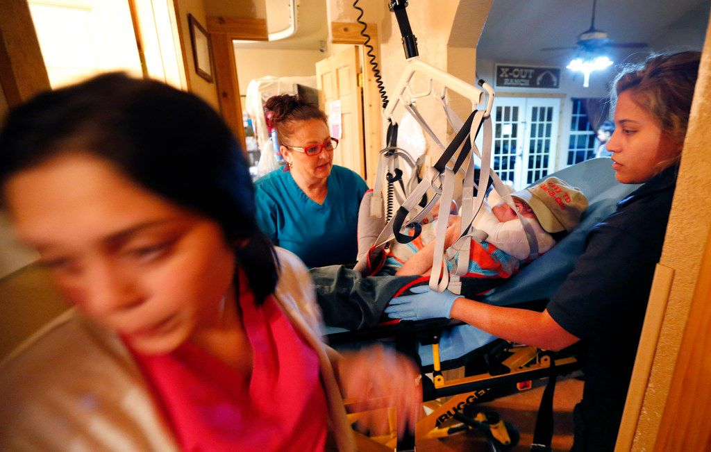 Foster mother Tammy Bolin (center) watches as the lift used to carry 23 yr-old Joseph Cano clears the hallway as she and LVN Elizabeth Lozano (left) move him back to his bed following his doctors appointment in San Antonio.  It takes a team of dedicated nurses and licensed practical nurses to pack, load and haul her five primary medical needs children back and forth 85 miles from her rural home in Mountain Home, Texas, Tuesday, June 6, 2017.