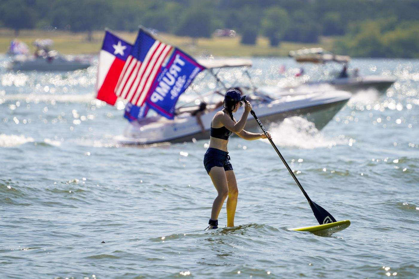 Boaters in support of President Donald Trump pass a woman on a paddle board as they parade around Grapevine Lake near Murrell Park on Saturday, Aug. 15, 2020.