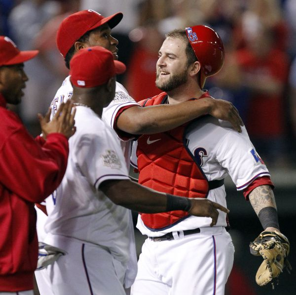 Rangers reliever Neftali Feliz (center) wraps up catcher Mike Napoli after closing down the Cardinals. Thanks to Napoli's two-run double in the eighth, Texas can wrap up its first World Series title Wednesday in St. Louis.