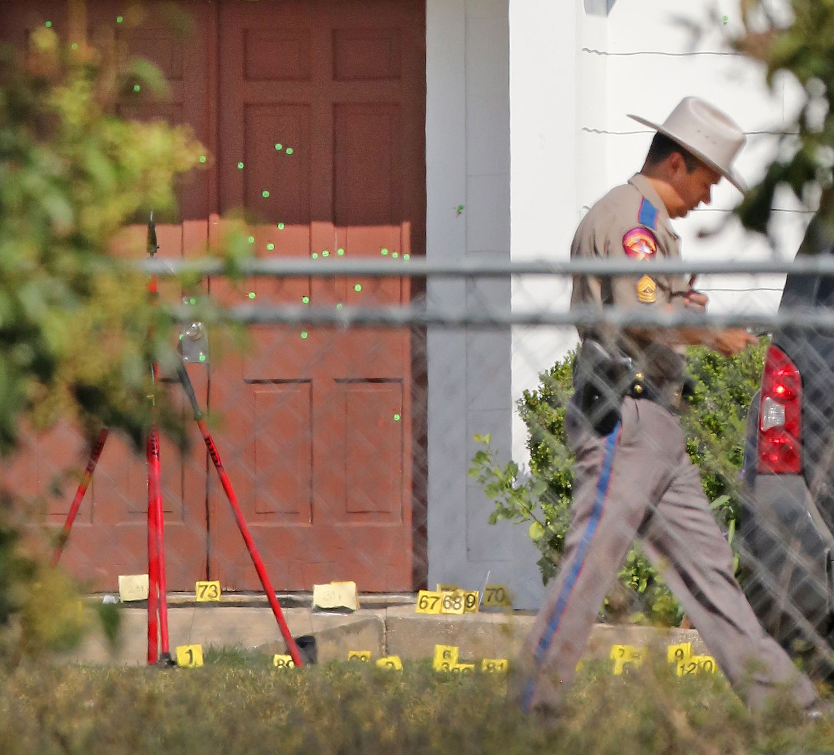 The front door of the First Baptist Church in Sutherland Springs shows multiple markings for bullet holes, with evidence of shell casings on the ground, as officials continue to investigate Sunday's shooting at a Baptist church in Sutherland Springs, Texas.