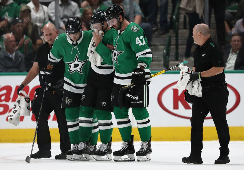 DALLAS, TEXAS - OCTOBER 03:   Blake Comeau #15 of the Dallas Stars is helped off the ice after a puck hit him in the face in the first period against the Boston Bruins at American Airlines Center on October 03, 2019 in Dallas, Texas. (Photo by Ronald Martinez/Getty Images)