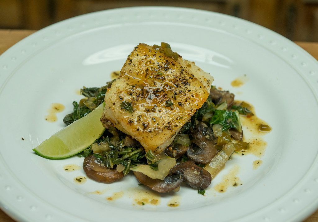 A Pan Seared Sea Bass arocet with compound butter, served atop sauteed Bok Choy and Shitake Mushrooms with Mirin glaze created by Mike Newton, known as the Cowboy Chef, in his ranch house kitchen in Lipan, Texas on July 17, 2018. (Robert W. Hart/Special Contributor)