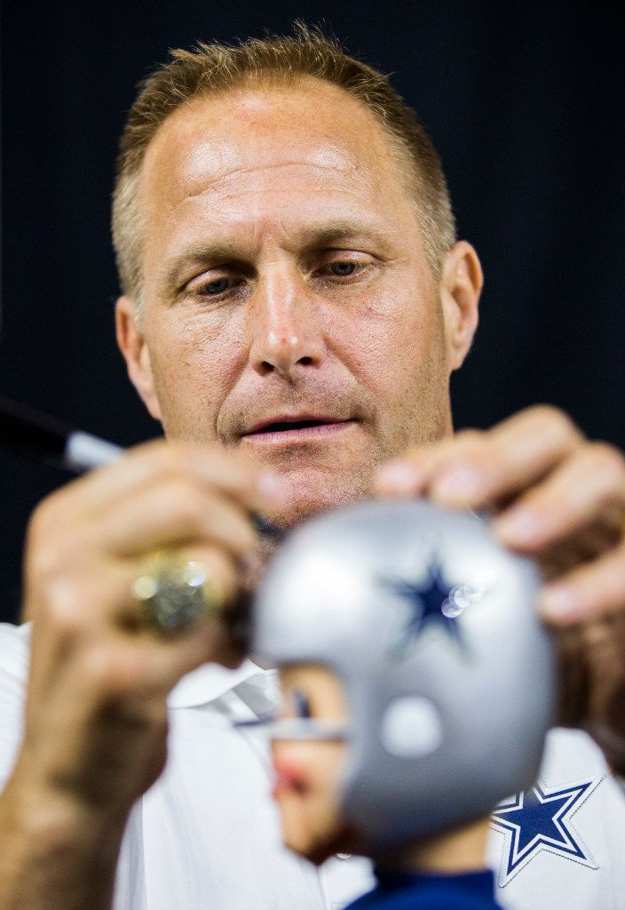 Former Dallas Cowboys defensive tackle Chad Hennings signed a bobblehead for a fan during the Dallas Cowboys' 2017 NFL Draft Party.