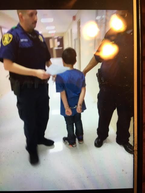 A student at Gabe P. Allen Charter School is handcuffed.