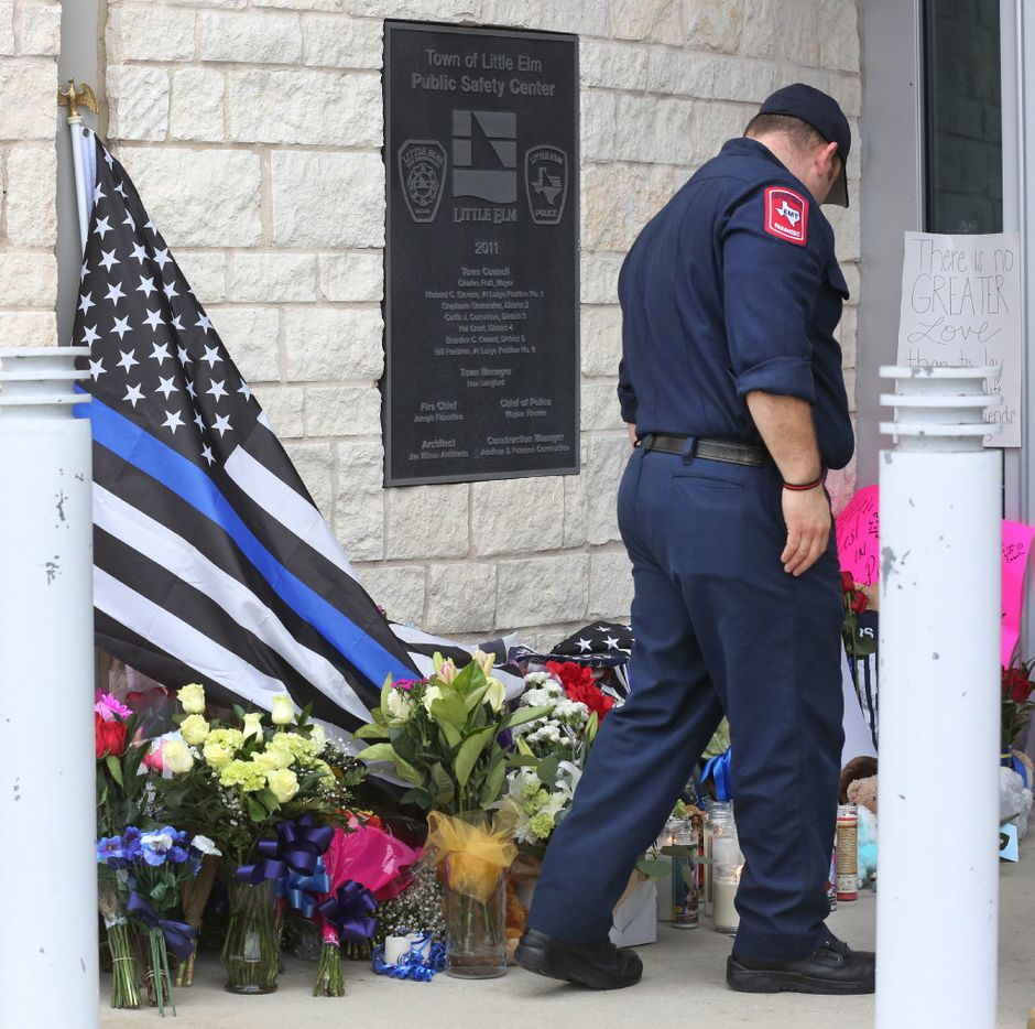 A Little Elm paramedic stands watch at the makeshift memorial at the Little Elm Police Department. (Louis DeLuca/Staff Photographer)