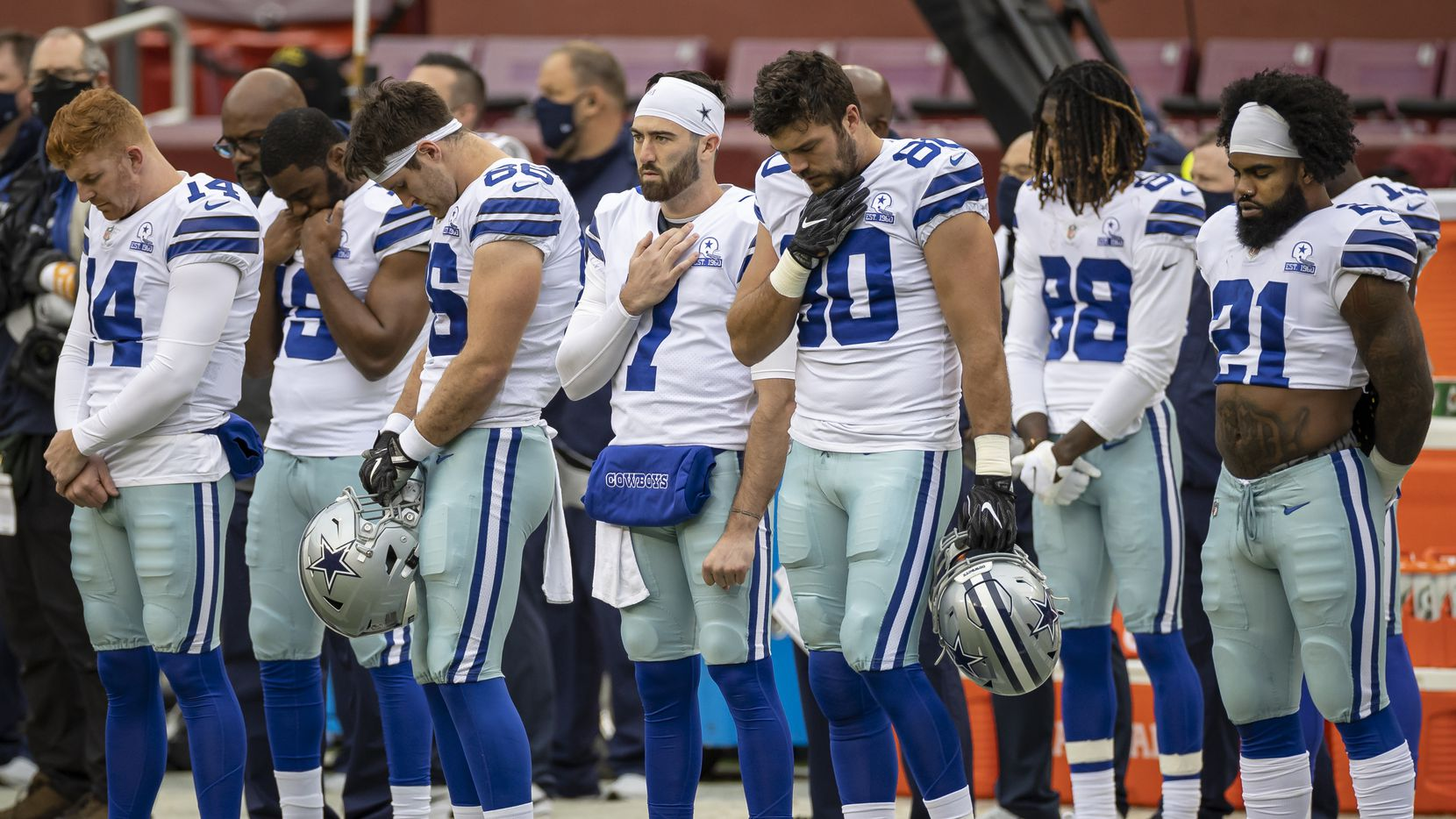 LANDOVER, MD - OCTOBER 25: Andy Dalton #14, Ezekiel Elliott #21, CeeDee Lamb #88, and Ben DiNucci #7 of the Dallas Cowboys stand with teammates during the playing of the National Anthem before the game against the Washington Football Team at FedExField on October 25, 2020 in Landover, Maryland.