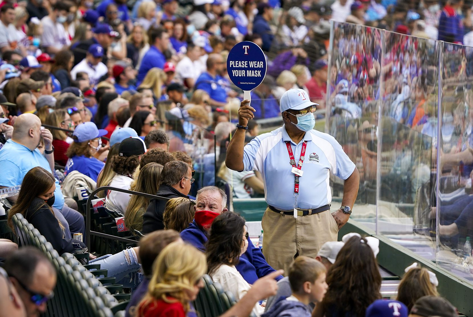 An usher holds a sign encouraging fans to wear face coverings between innings of a game between the Texas Rangers and the Baltimore Orioles at Globe Life Field on Sunday, April 18, 2021.