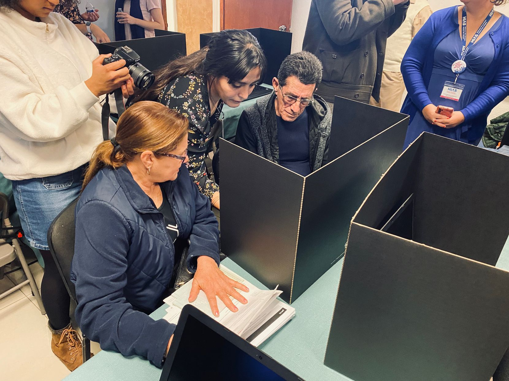 A legal worker helped asylum seekers Ramón Piniero Alvarez and his wife, Mirta Matilde Alvarez, sign on to a computer to seek legal assistance from a U.S.-based attorney Tuesday in Ciudad Juarez, Mexico.