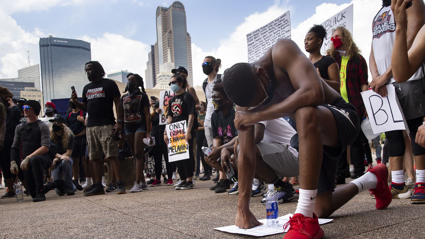 """Ryan Hunter of Fort Worth kneels at Dallas City Hall after peacefully marching through downtown Dallas demonstrating against police brutality on June 2, 2020. """"I'm tired of seeing people that look like me dead in the streets,"""" Hunter said."""