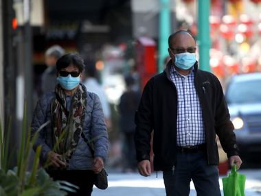 People wear surgical masks as they walk along Chinatown's Grant Avenue on Wednesday in San Francisco.