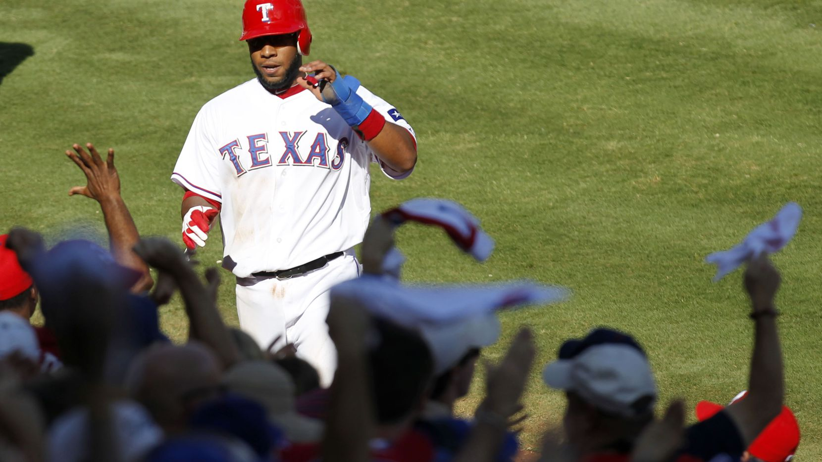 Texas Rangers shortstop Elvis Andrus walks into the dugout after scoring on a double by Josh Hamilton in the second inning of Game 2 of the American League Championship Series against the Detroit Tigers at Rangers Ballpark in Arlington, Monday, Oct. 10, 2011.  (Vernon Bryant/The Dallas Morning News)